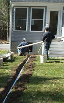 exterior discharge line being installed across the lawn from the house